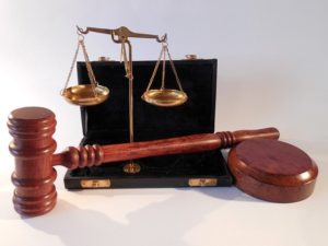 Scales of justice next to a gavel and block